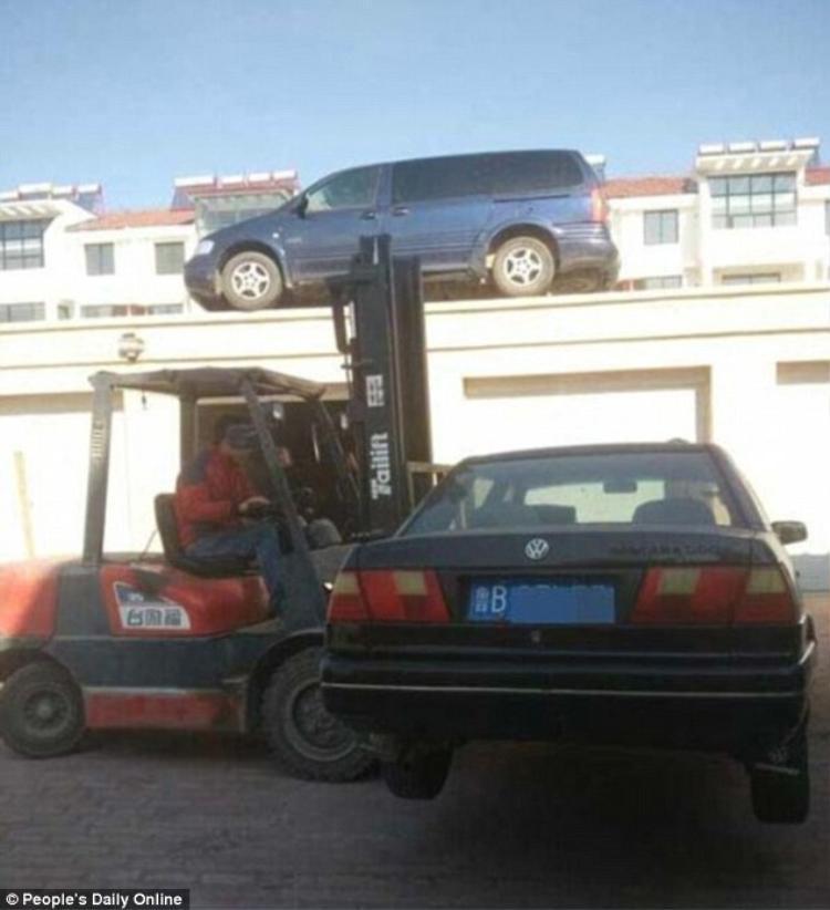 Người đàn ông đang cẩu những chiếc xe đỗ sai quy định lên nóc nhà.