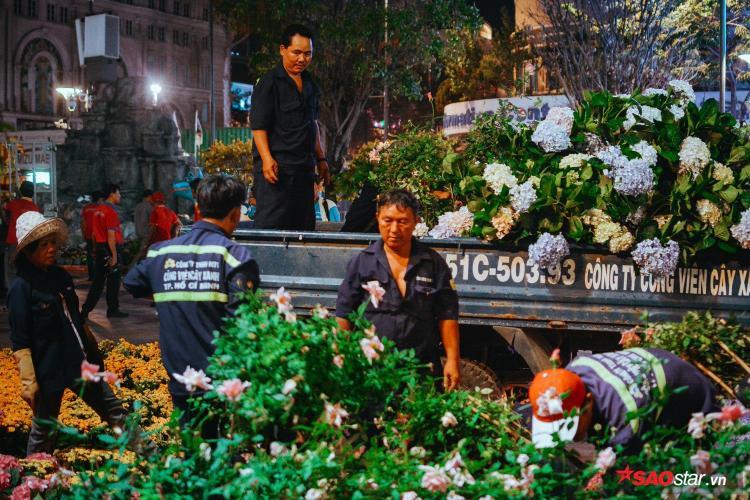 22h ngày mồng 4 Tết, đường hoa Nguyễn Huệ chính thức bế mạc. Hàng trăm công nhân tất bật thu dọn ngay trong đêm.