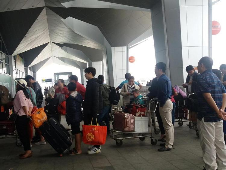 Các hành khách xếp hàng vào sân bay.