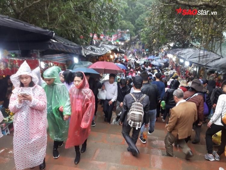 Thời tiết mưa xuân nên khi trẩy hội, người dân phải mặc áo mưa, mang ô.