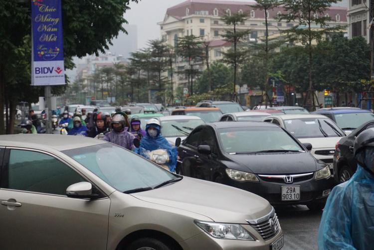 Tại đường Trung Kính, quận Cầu Giấy cảnh xe máy len lỏi vì ách tắc trong ngày đầu năm.
