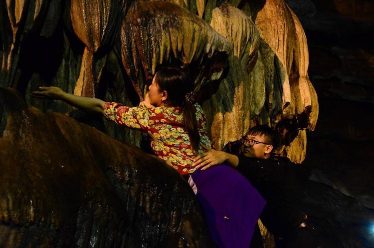 """Thậm chí, nhiều người bất chấp nguy hiểm để hứng """"nước lộc"""" ở vách núi cheo leo, hay vô tư ngồi lên đầu rùa."""