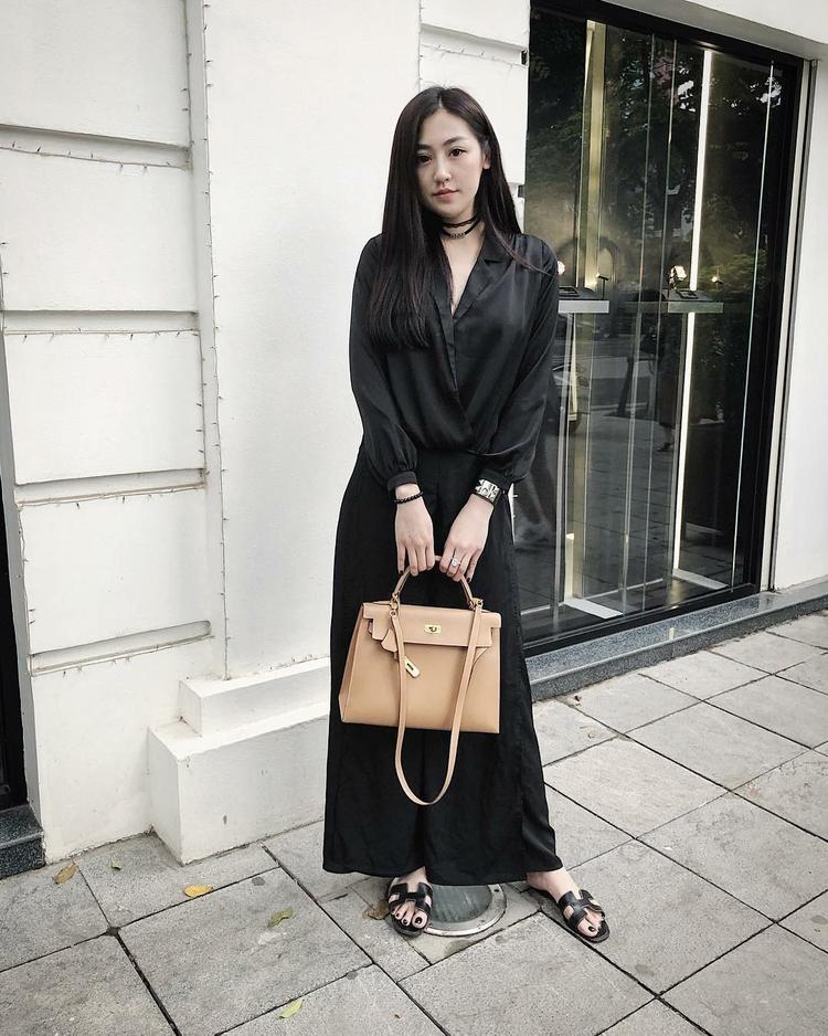 Dương Tú Anh thùy mị trong chiếc váy maxi đơn sắc full đen cùng túi xách màu be to bản khá cổ kính.
