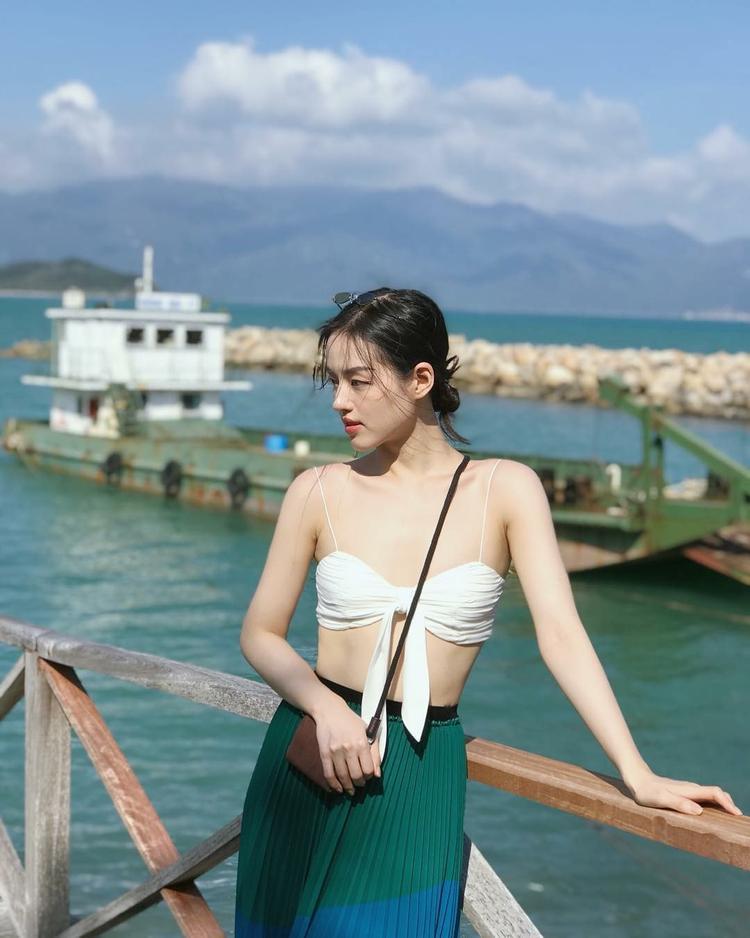 """Cô nàng Khánh Linh """"The Face"""" đang tận hưởng một kì nghỉ tuyệt vời tại Nha Trang. Người đẹp khoe """"mình hạc sương mai"""" với một chiếc croptop trắng mix với váy xếp ly xanh sẫm."""