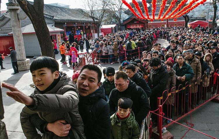 Rất đông người dân Trung Quốc, trong đó có cả trẻ nhỏ, kiên nhẫn xếp hàng dài tại chùaBaiyun Taoist ở Bắc Kinh để được tiếp cận và chạm tay vào tượng khỉ đá lấy may trong những ngày đầu năm mới.