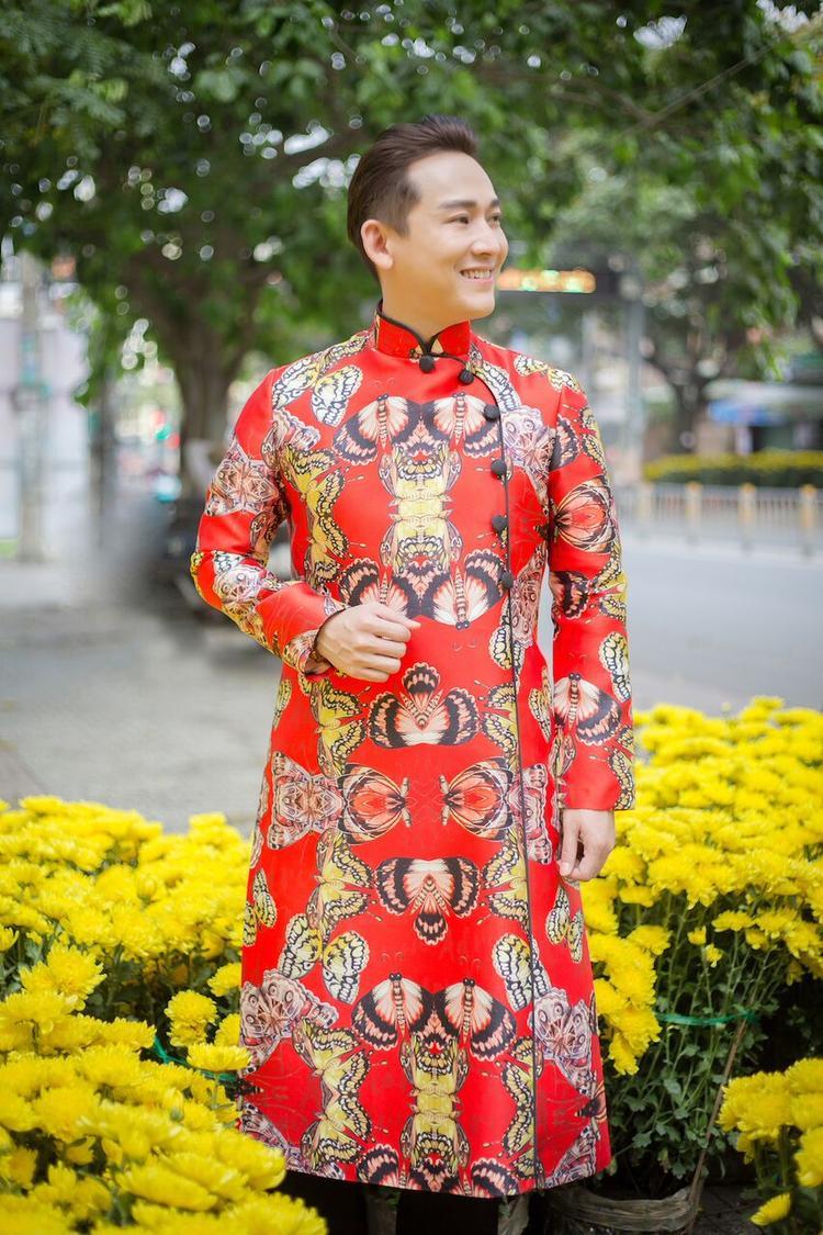 """Trang phục sở hữu những đường nét và phong cách hiện đại, nhưng vẫn giữ được phom dáng truyền thống của chiếc áo dài. Tông đỏ tươi cùng hình ảnh những cánh bướm giúp """"soái ca"""" trở thành tâm điểm khi xuống phố."""