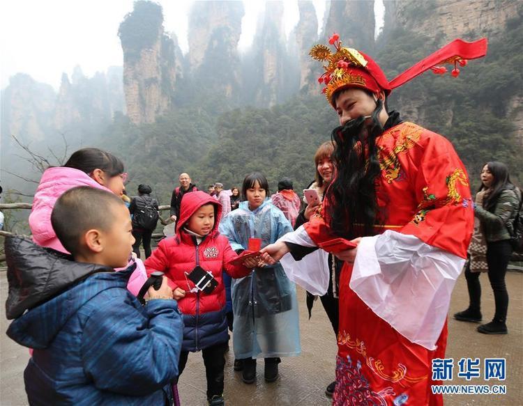 Ông Thần Tài phát phong bao lì xì đỏ cho các em nhỏ để lấy may đầu năm.