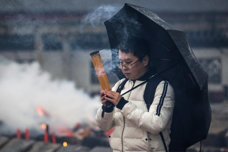 Một người đàn ông đang cầm cả bó hương để cúng Thần Tài.