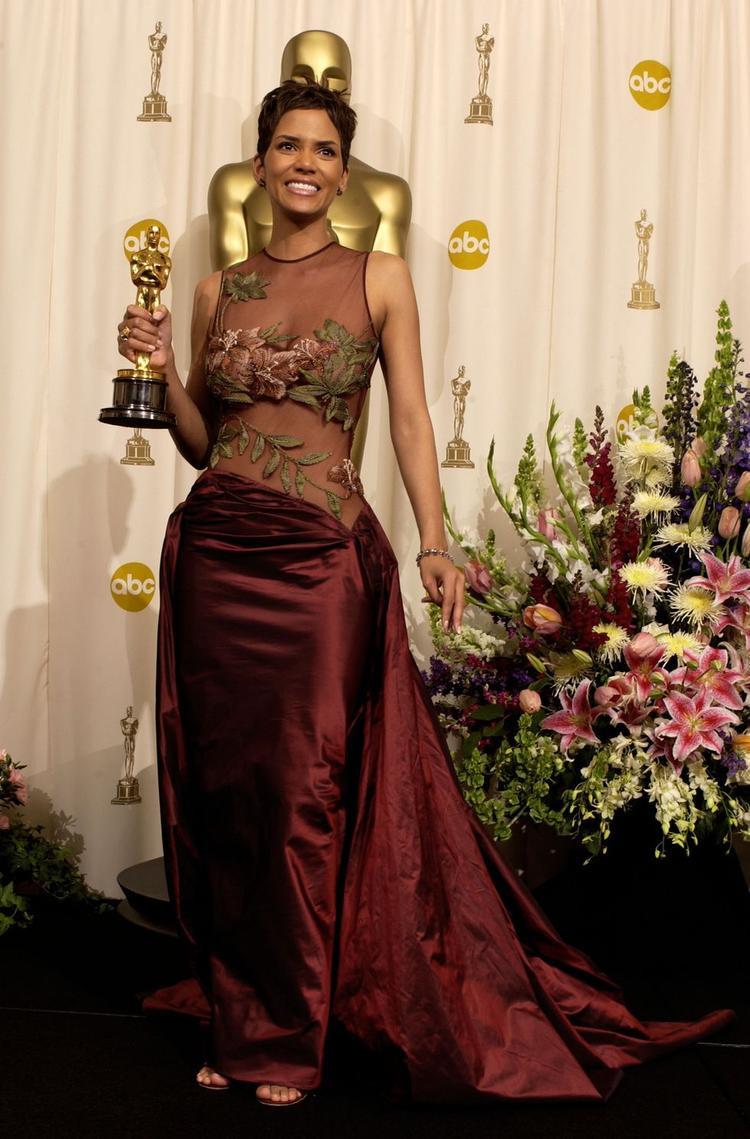 """Chiếc váy màu tía trong suốt Elie Sab đã giúp Halle Berry tỏa sáng trên thảm đỏ năm 2002. Họa tiết hoa được thêu khéo léo ở vị trí """"chiến lược"""" giúp khổ chủ gợi cảm một cách tinh tế. Cô là người phụ nữ da đen đầu tiên được nhận giải thưởng Nữ diễn viên xuất sắc nhất cho vai diễn trong Monster's Ball."""