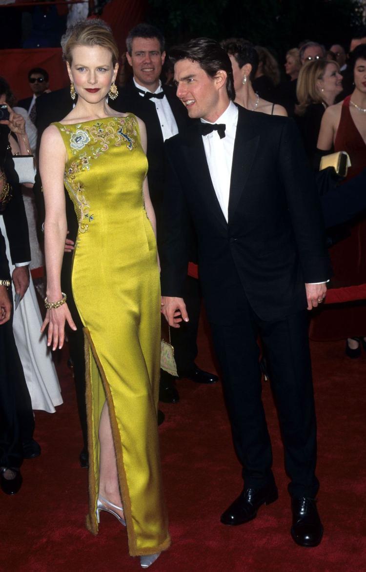 """Nicole Kidman không ngần ngại diện chiếc đầm vàng vô cùng """"chói"""" với màu thảm đỏ. Thế nhưng chính điều đó đã làm cô nổi bật nhất trong đêm trao giải khi đến xem chồng - Tom Cruise nhận giải. Chiếc đầm là một trong những thiết kế đặc biệt nhất của nhà mốt Dior lúc bấy giờ."""