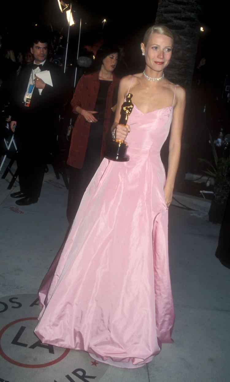 """Gwyneth Palthrow đã diện chiếc đầm công chúa của nhà mốt Ralph Lauren khi vinh danh nhận giải diễn viên xuất sắc nhất cho vai diễn trong phim """"Shakespeare in Love"""". Màu sắc đơn giản nhẹ nhàng khó quên này đã giúp cô trở thành một trong những biểu tượng khó quên trên thảm đỏ Oscar."""