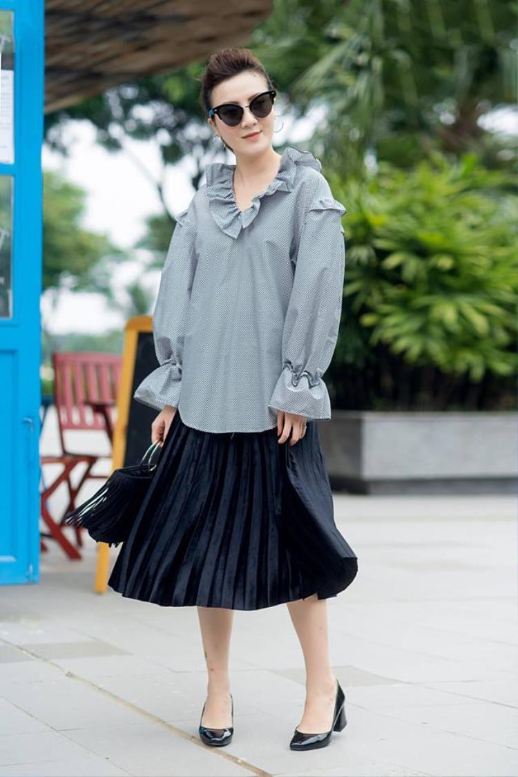 Yến Nhi cũng cập nhật ngay xu hướng này với áo sơ mi bèo nhún và chân váy xếp ly cực nữ tính.