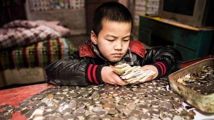 Li đang đếm số tiền lẻ mà cậu bé dành dụm trong 2 năm qua.