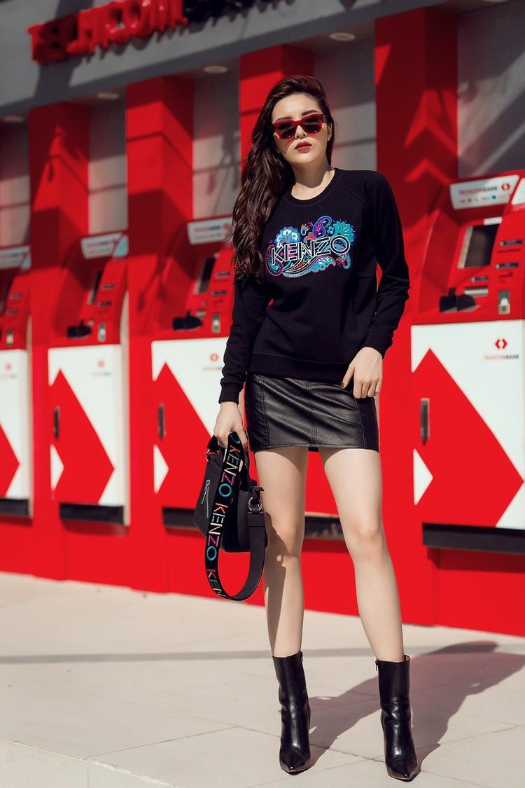 Nàng Hậu diện cả cây đen nhưng vẫn nổi bật, cô diện nguyên set của thương hiệu Kenzo bao gồm áo, chân váy và túi xách. Phụ kiện boot đắt giá từ thương hiệu thời trang cao cấp vetements và mắt kính đỏ của Celine.