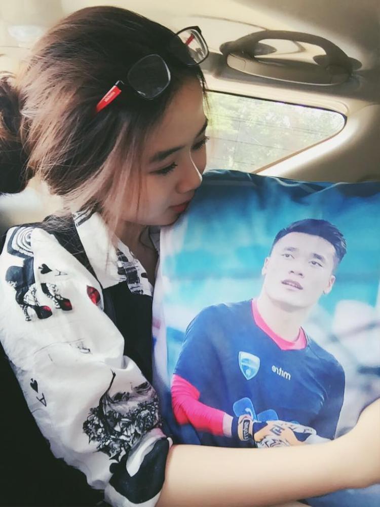 Một fan nữ ôm chiếc gối có hình thủ môn Bùi Tiến Dũng.
