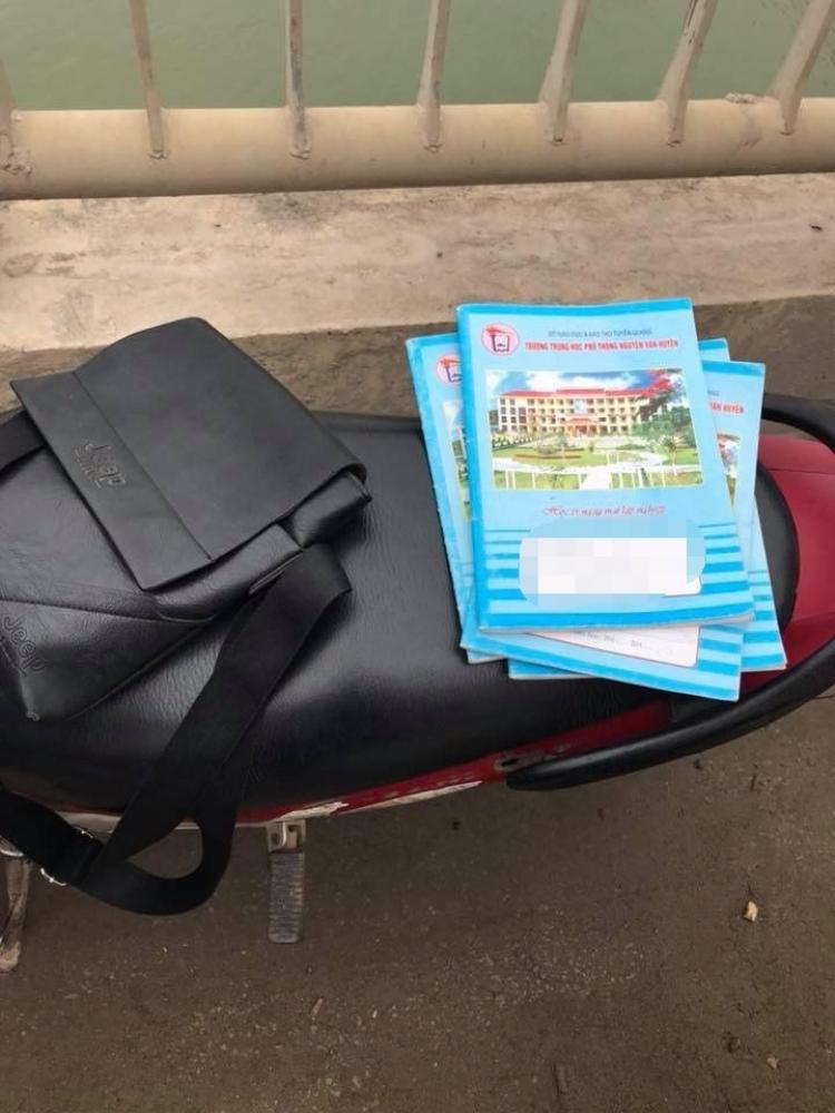 Cặp sách cùng xe máy của nam sinh để lại trên thành cầu.