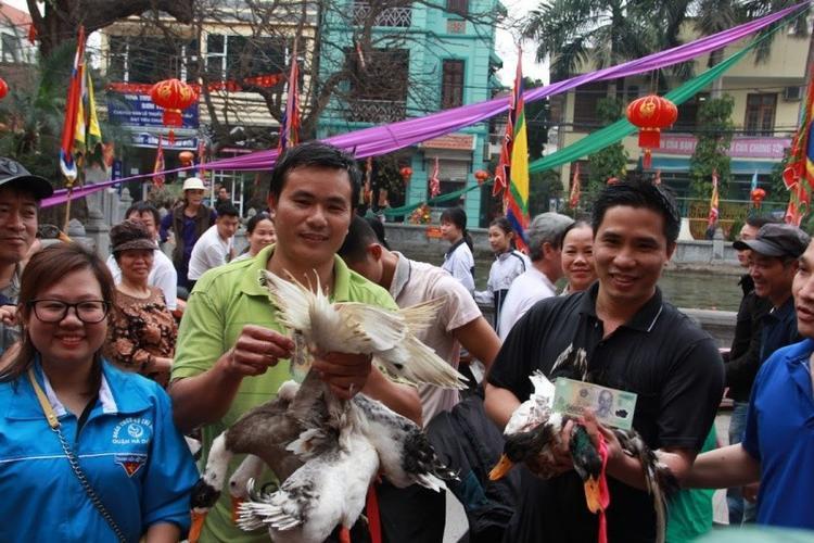 Anh Nguyễn Chí Thành (áo đen, tổ dân phố Hạnh Phúc) đã hai lần tham gia trò chơi và bắt được hai con vịt. Anh cùng anh Đồ vui vẻ nhận phần thưởng của Ban tổ chức.