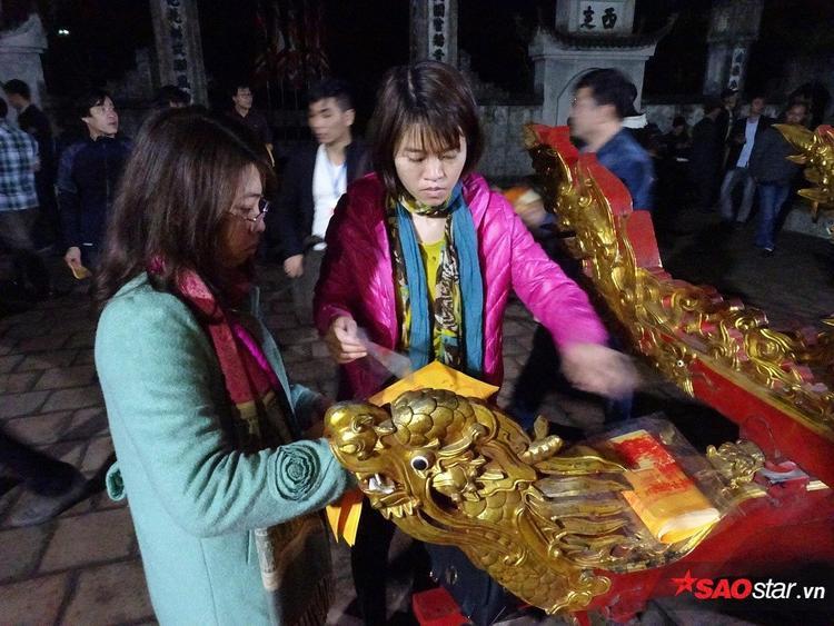 Hai người phụ nữ này cũng vừa xin được ấn, họ đang soạn sửa cẩn thận từng cánh ấn.