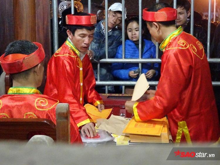 Tại các khu vực phát ấn trước đền Thiên Trường, người phát ấn gần như phải làm việc hết công suất.