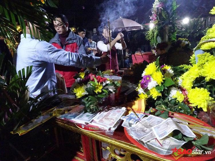 Những người đến xin ấn khấn tạ ơn các vị vua Trần, nhiều tiền lẻ được người dân đặt lễ.