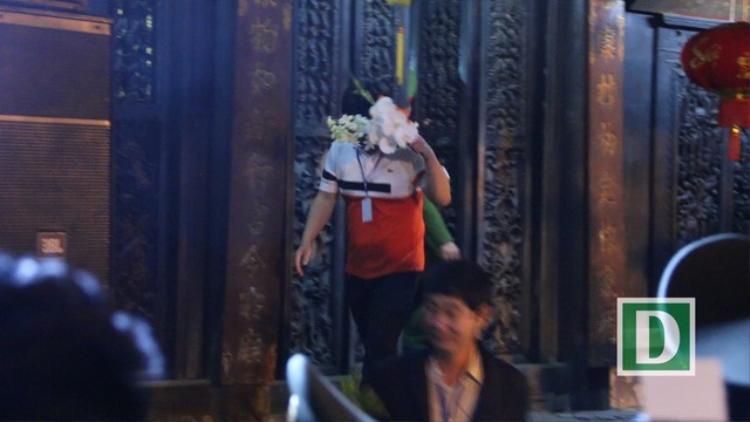 """Khi thấy ống kính phóng viên hướng về phía mình, người đàn ông này ngay lập tức dùng """"chiến lợi phẩm"""" là """"lộc xin"""" được trong đền Thiên Trường che lên mặt"""