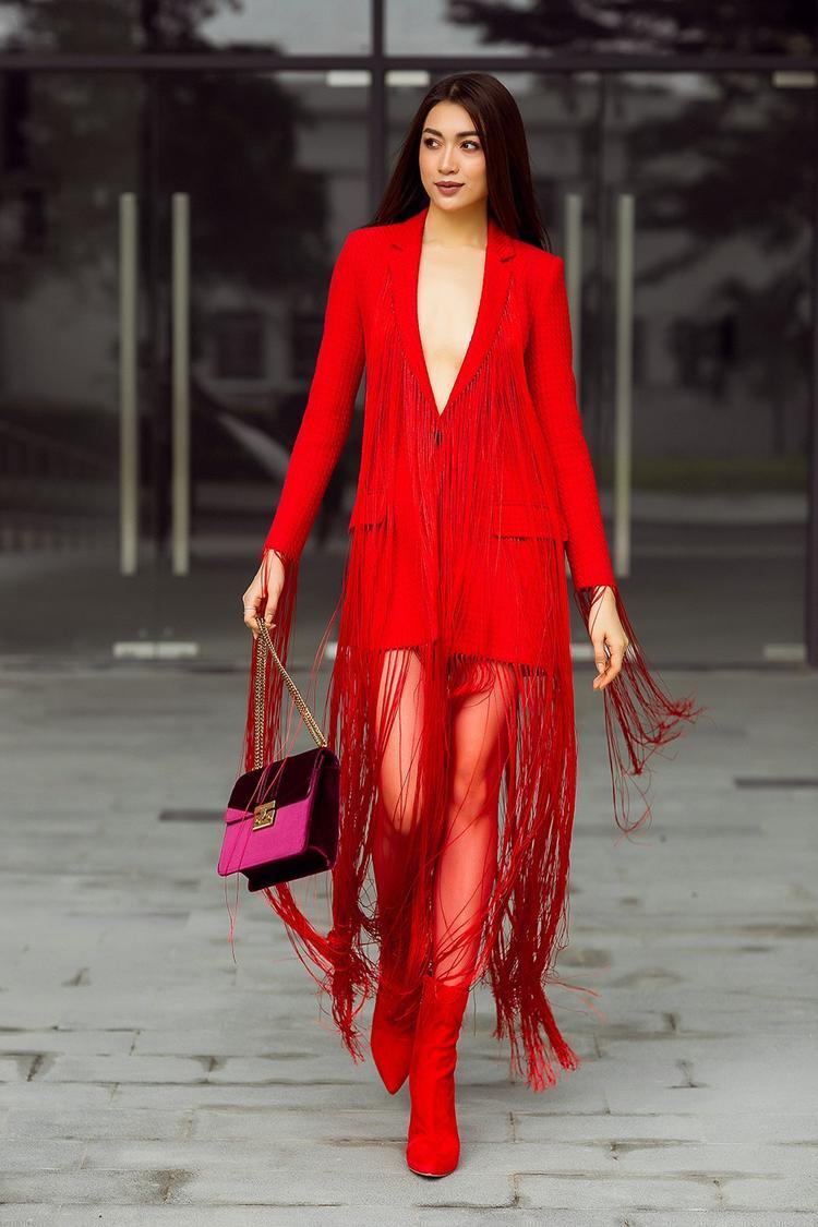 Chi tiết tua rua kết hợp dáng shirt dress năng động mang đến sự giao thoa giữa hình ảnh thanh lịch và cá tính cho người mặc. Đi kèm trang phục lại là chiếc túi nhung có sắc đỏ tím ngọt ngào.