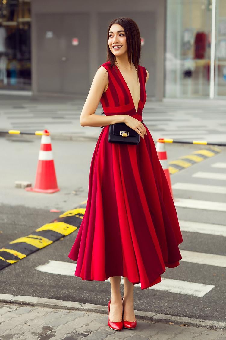 Dáng váy xòe cổ điển được Đỗ Mạnh Cường làm mới với đường xẻ ngực sâu cùng sự kết hợp hai tông màu sáng, tối với cùng sắc đỏ thú vị.