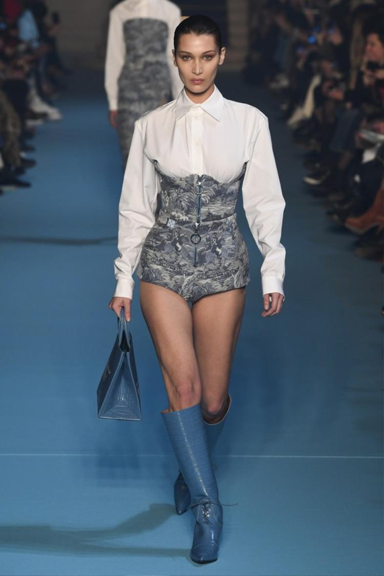 Bella Hadid là người mẫu được vinh dự mở màn show diễn. Diện một thiết kế gồm sơ mi trắng tay bồng đóng thùng cùng corset cách điệu. Siêu mẫu người Mỹ khoan thai sải những bước chân chắc nhịp giữa tiếng vỗ tay của toàn thể khán giả.