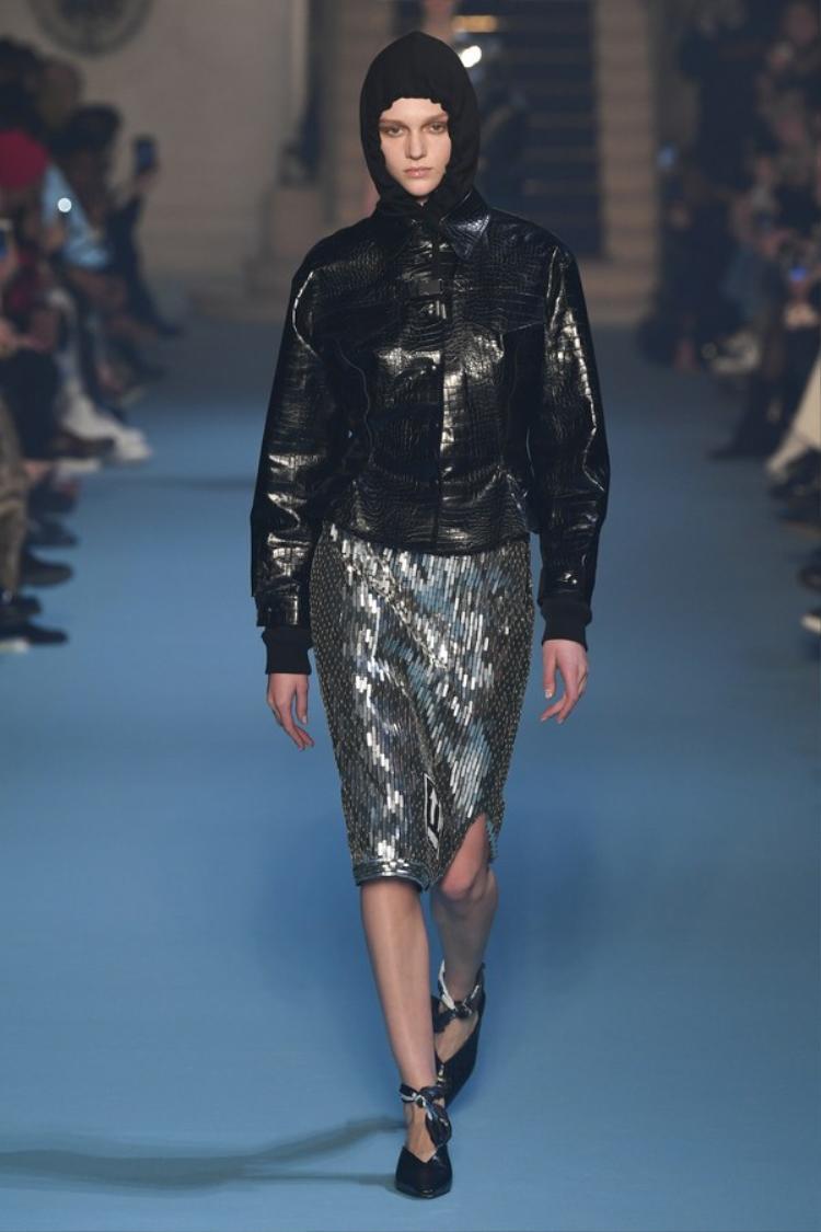 Một thiết kế áo khoác trùm đầu với chất liệu da bóng hiện đại kết hợp chân váy sequin đính kết.