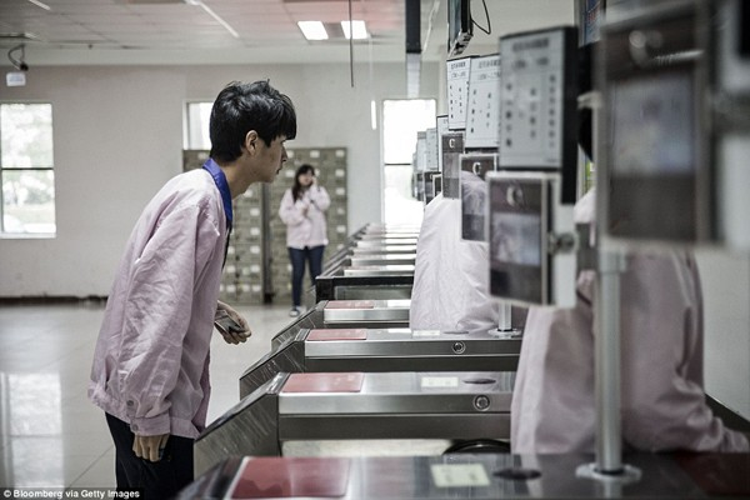 Một công nhân nhìn vào máy nhận diện khuôn mặt, điều mà tất cả công nhân cần làm trước khi bước chân vào khu vực lắp ráp.