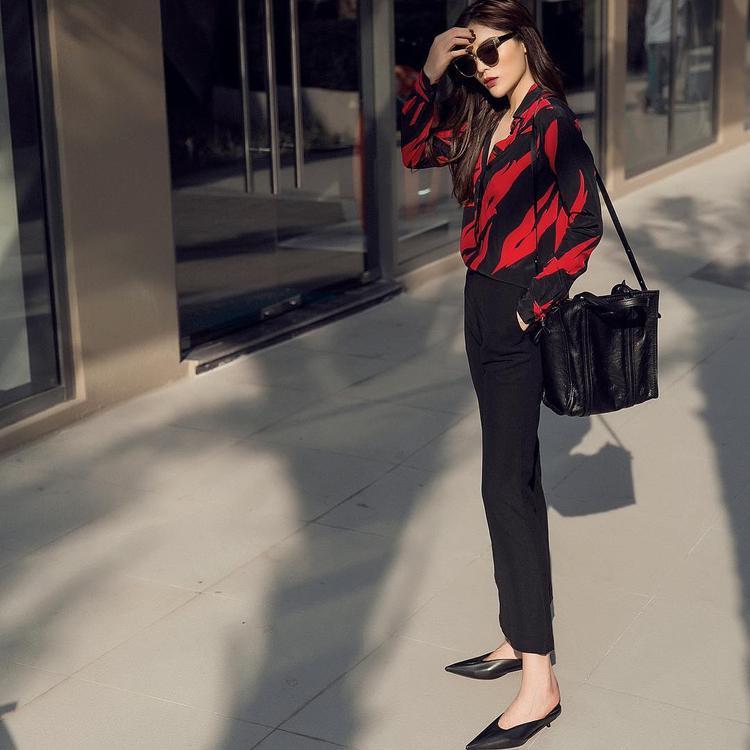 Với chiếc áo sơ mi của Saint Laurent trị giá 13,5 triệu đồng, Kỳ Duyên thật sự tỏa sáng khi xuống phố. Hoa hậu Việt Nam 2014 phối cùng quần tây đen, mang giày cổ chữ V, gót thấp xu hướng 2018 cùng kính mát đen nhằm tạo ra vẻ ngoài thời thượng.