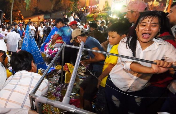 """Đến khoảng 23h50, một góc hàng rào """"thất thủ"""" khi dòng người chen nhau xô đẩy gãy đổ các cây tre. Lực lượng an ninh đành phải dạt ra cho hàng trăm người ùa vào cùng lúc.Ảnh: VnExpress."""