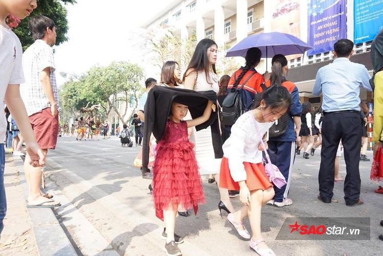 Các em nhỏ lấy áo khoác làm áo tránh nắng khi dạo phố đi bộ.