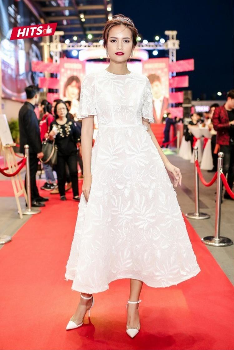 Cả cây trắng là sự lựa chọn của Ngọc Châu - Quán quân Next Top 2016. Chất liệu vải có độ đơ vừa phải tạo nên phần tùng váy xòe nhẹ nhàng, bay bổng. Để ăn-rơ với trang phục, cô nàng cũng lựa chọn cao gót mũi nhọn, có quai mảnh làm nên tổng thể hài hòa.