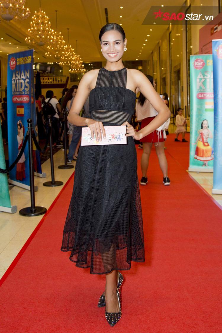 """""""Ngọc trai đen"""" H'ăng Niê chọn cho mình bộ váy đen với thiết kế cắt cúp hiện đại, trẻ trung đúng với tính cách của cô. Người đẹp gốc Ê-đê cũng phối cùng đôi giày đen, đính kim loại cá tính nhằm hoàn thiện tổng thể."""