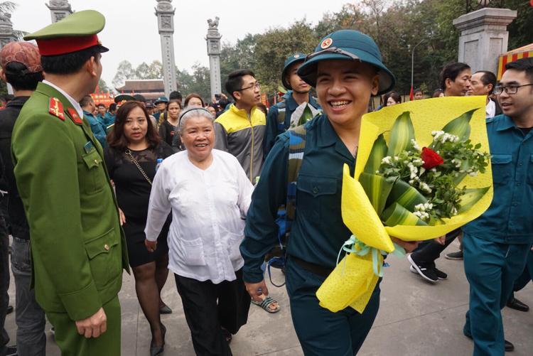 Chàng tân binh vui vẻ lên đường nhận nhiệm vụ, theo sau là bà cùng người thân.