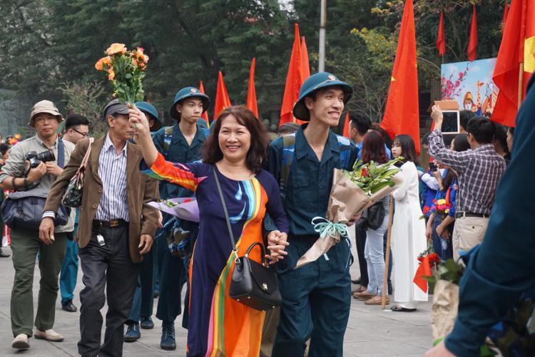 Người mẹ này vui mừng cầm hoa tiễn con trai lên đường nhập ngũ.