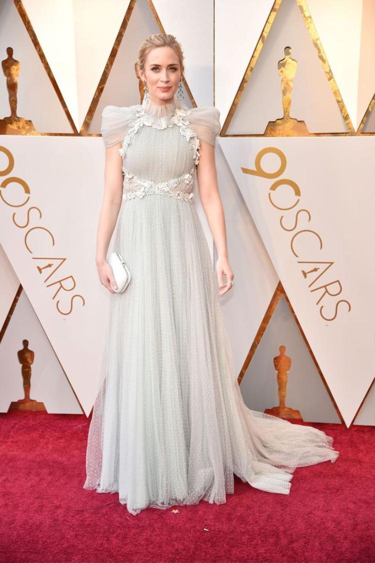 Emily Blunt chọn thiết kế màu pastel nữ tính với điểm nhấn nằm ở phần cầu vai. Trang phục của cô thuộc BST Haute Couture xuân 2018 của nhà mốt Schiaparelli.