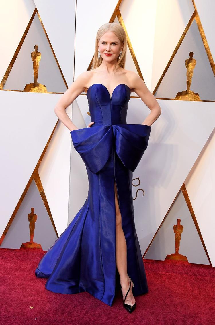 Nicole Kidman khoe vóc dáng đáng ngưỡng mộ ở tuổi 50 trong thiết kế tinh xảo của Armani Privé.Những đường cúp ngực được cắt xẻ khéo léo, chiếc nơ xanh làm điểm nhấn cho tổng thể.