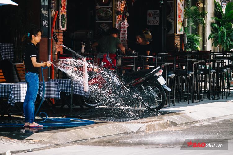 Cửa hàng trên phố tây Bùi Viện đồng loạt xịt nước giữa trưa để giảm bớt sức nóng được mặt đường nhựa bốc lên.