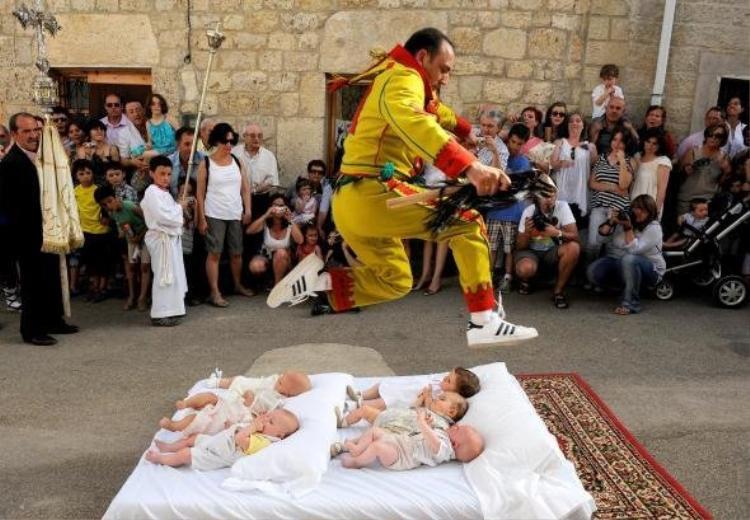 Những người đàn ông trong trang phục tượng trưng cho ma quỷ sẽ nhảy qua những đứa trẻ được đặt trên nệm để mang lại may mắn cho chúng. Ảnh: nationalgeographic