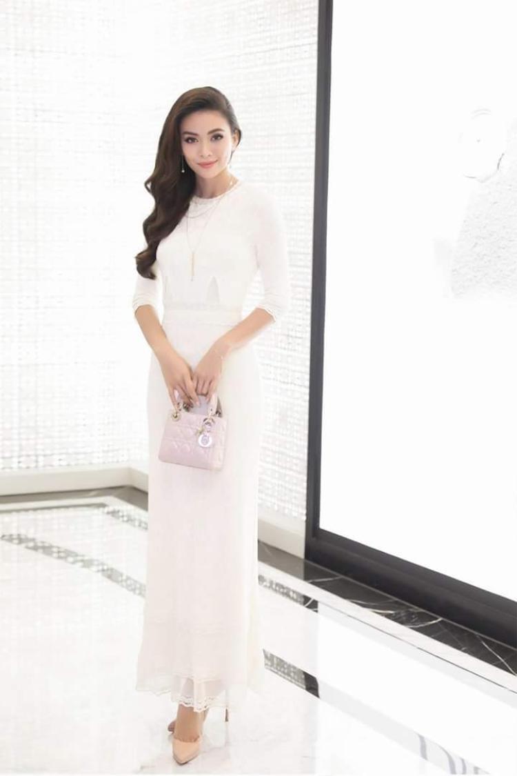 Mâu Thủy khoe vẻ đẹp ngọt ngào, nữ tính đúng chất hoa hậu. Cô nàng lựa chọn chiếc váy trắng dài ôm sát, đi cùng túi xách Lady Dior đắt giá.