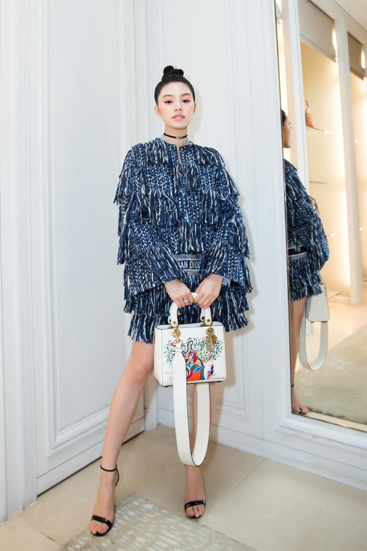 Bộ cánh chất liệu bố đan là lựa chọn của Jolie Nguyễn khi tham dự event. Điểm nhấn trang phục là chiếc túi xách màu trắng có họa tiết vui nhộn.