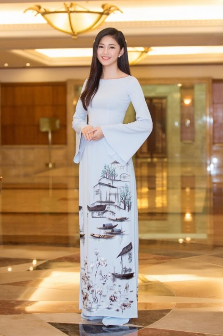 Á hậu 1 Hoa hậu Việt Nam 2016 Ngô Thanh Thanh Tú mặc chiếc áo dài màu xanh nhạt với họa tiết hoa sen xinh xắn.