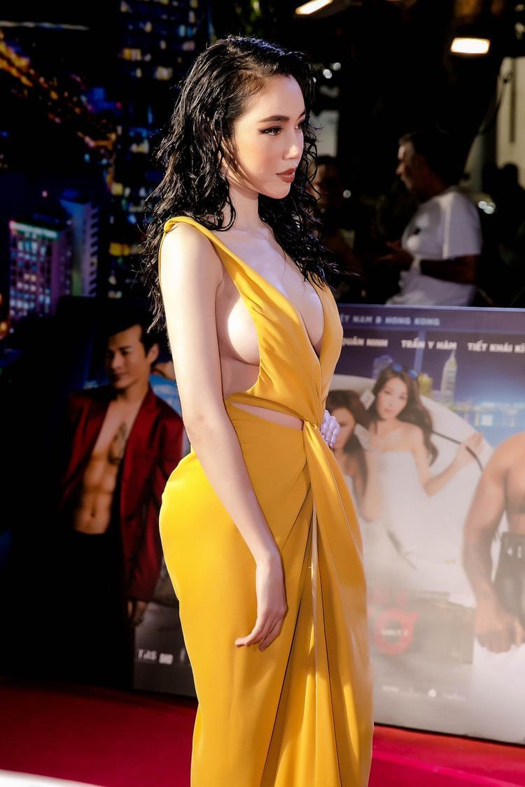 Chiếc váy màu vàng của NTK Hoàng Minh Hà với những đường cắt xẻ táo bạo giúp Elly Trần khoe khéo vòng một gợi cảm cùng làn da trắng ngần.
