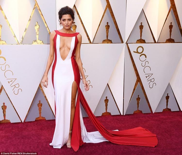 Nữ diễn viên Blanca Blanco gây chú ý khi xuất hiện trên thảm đỏ Oscar với bộ đầm xẻ cao, khoét ngực táo bạo. Không những thế, trang phục còn có khoảng hở lớn ở phía sau. Chiếc váy hai màu đỏ - trắng khá nổi bật nên Blanco chọn phụ kiện, trang sức tối giản.