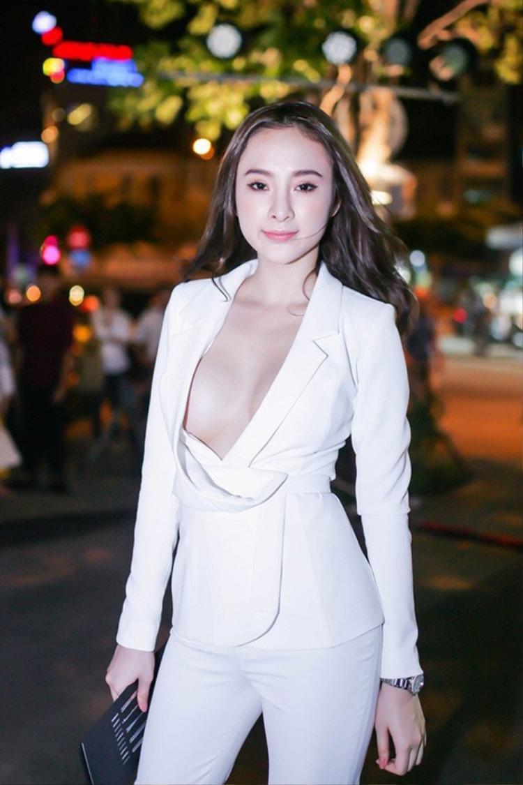 """Trong trang phục suit trắng, Angela Phương Trinh """"gây bão"""" bởi thiết kế phần cổ áo quá sâu để lộ nguyên vòng một căng tròn."""