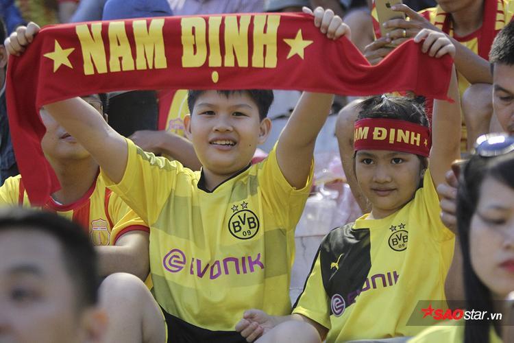 """Hai fan nhí liên tục giơ khăn choàng với dòng chữ """"Nam Định"""" để cổ vũ."""