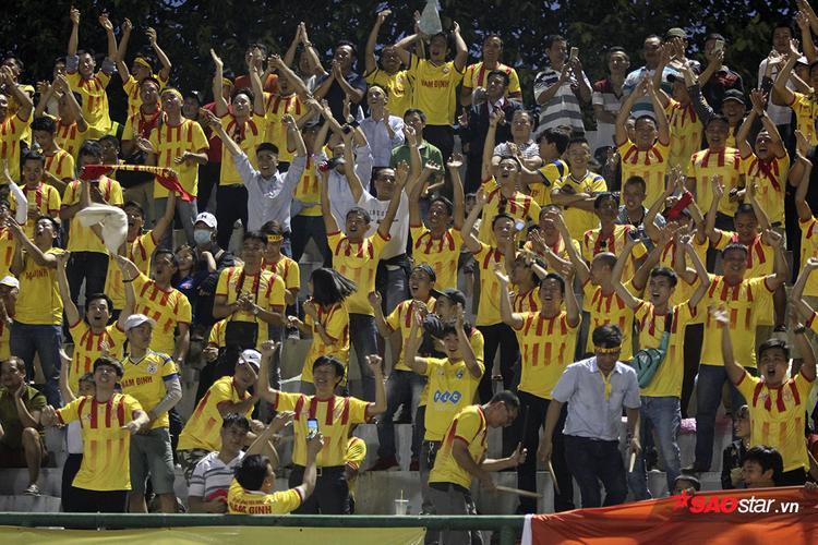 """Người hâm mộ Nam Định phấn khích ăn mừng bàn thắng. Sau bàn rút ngắn, không khí trên khán đài càng """"rực lửa"""" hơn. Có cảm giác như Nam Định đang chơi trên chính sân nhà của mình."""