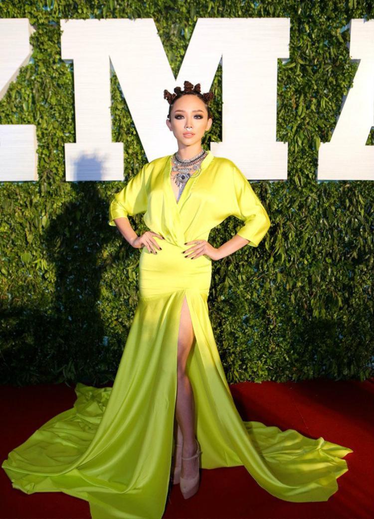 Thiết kế của Lý Quí Khánh cũng nhiều lần giúp Tóc Tiên nổi bật trên thảm đỏ. Trong ảnh cô diệnmẫu xiêm y màu vàng óng ánh của với những đường cắt xẻ táo bạo giúp đôi chân trần được khoe một cách khéo léo.